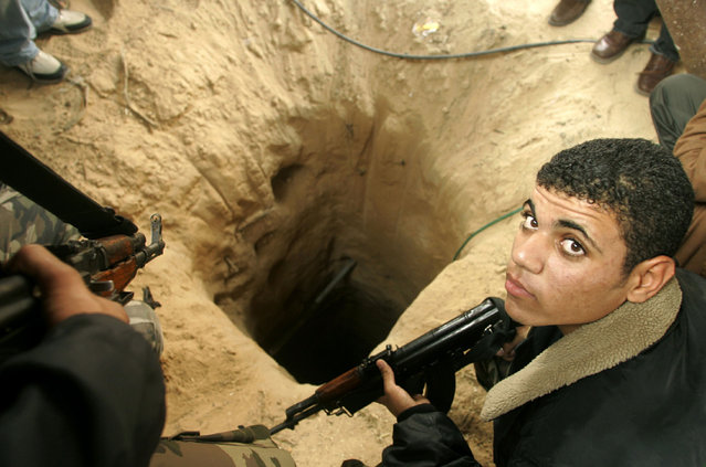 A Palestinian security officer prepares to seal a tunnel used to smuggle arms during an operation next to the border with Egypt at the Rafah refugee camp in the southern Gaza Strip December11, 2005. (Photo by Mohammed Salem/Reuters)