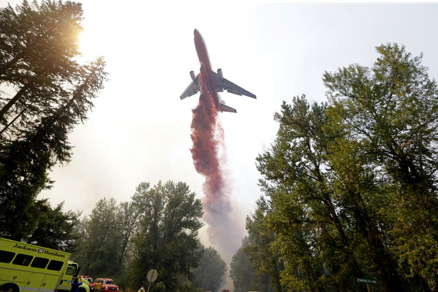 A tanker drops fire retardant on a fire that flared-up Thursday, August 20, 2015, in Twisp, Wash. ildfires rampaged across the drought-choked West on Thursday as authorities scrambled for resources to beat back the flames. (Photo by Elaine Thompson/AP Photo)