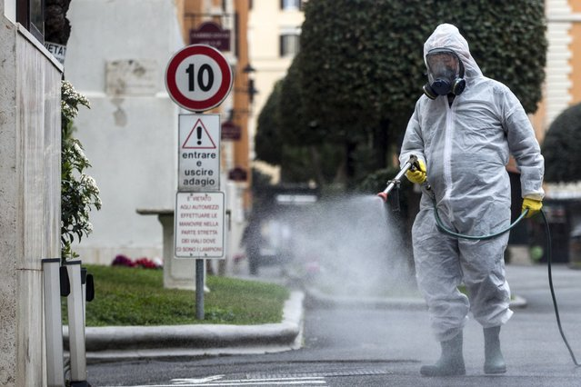A man carries out sanitization operations at a neighborhood during the emergency lockdown due to the Covid-19 Coronavirus outbreak in Rome, Italy, 14 March 2020. (Photo by Angelo Carconi/EPA/EFE)