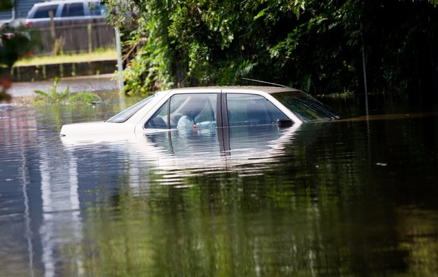A car is abandoned on a flooded Brooke Ave following heavy rains and flash flooding on  August 13, 2014 in Bayshore, New York. The south shore of Long Island along with the tri-state region saw record setting rain that caused roads to flood entrapping some motorists. (Photo by Andrew Theodorakis/Getty Images)