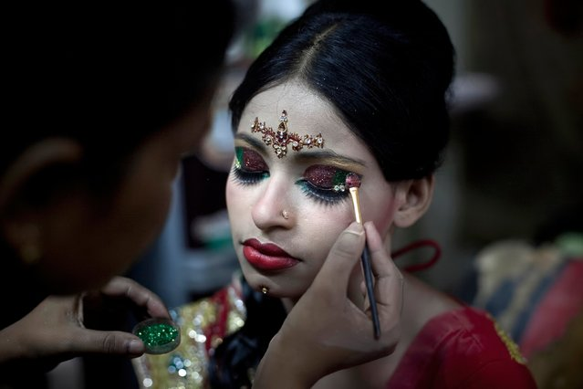 Nasoin Akhter, 15, has her makeup done at a beauty parlor on the day of her wedding to a 32-year-old man, August 20, 2015, in Manikganj, Bangladesh. (Photo by Allison Joyce/Getty Images)