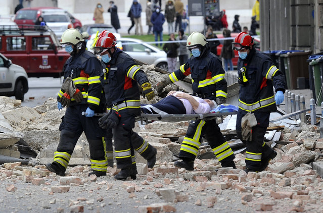 Firefighters carry a person on a stretcher after an earthquake in Zagreb, Croatia, Sunday, March 22, 2020.  A 5.3-magnitude earthquake shook the Croatian capital of Zagreb on March 22, 2020, damaging buildings and cutting electricity in a number of neighbourhoods. (Photo by AP Photo/Stringer)