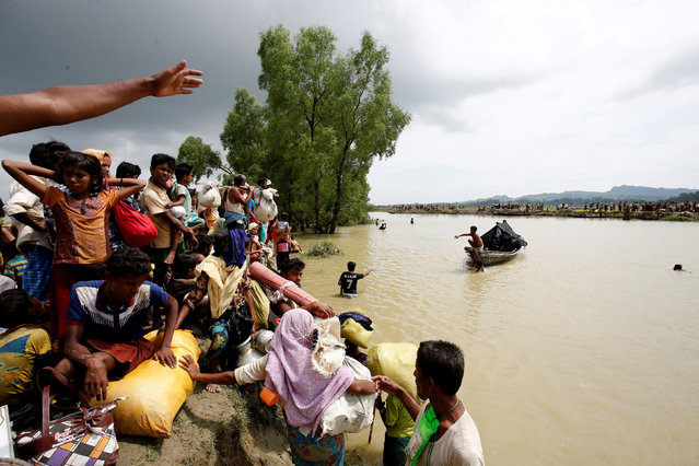 Rohingya refugees wait for boat to cross a canal after crossing the border through the Naf river in Teknaf, Bangladesh, September 7, 2017. (Photo by Mohammad Ponir Hossain/Reuters)