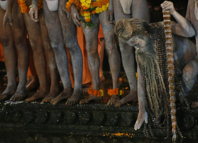 Naked Hindu holy men wait to bath in the Godavari River during Kumbh Mela, or Pitcher Festival, at Trimbakeshwar in Nasik, India, Saturday, August 29, 2015. Hindus believe taking a dip in the waters of a holy river during the festival, will cleanse them of their sins.  According to Hindu mythology, the Kumbh Mela celebrates the victory of gods over demons in a furious battle over a nectar that would give them immortality. (Photo by Rajanish Kakade/AP Photo)