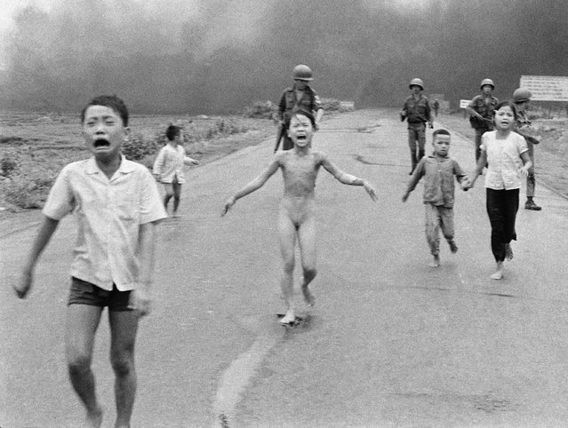 South Vietnamese forces follow after terrified children, including 9-year-old Kim Phuc, center, as they run down Route 1 near Trang Bang after an aerial napalm attack on suspected Viet Cong hiding places on June 8, 1972. (Photo by Nick Ut/AP Photo)