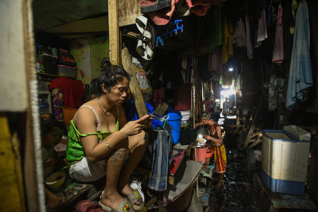 This photo taken on March 18, 2020 shows a woman checking her phone outside her home in Manila. Asian nations have imposed increasingly heavy measures to fight the outbreak of the COVID-19 coronavirus, the Philippines has ordered half its population of some 110 million to stay home. (Photo by Maria Tan/AFP Photo)