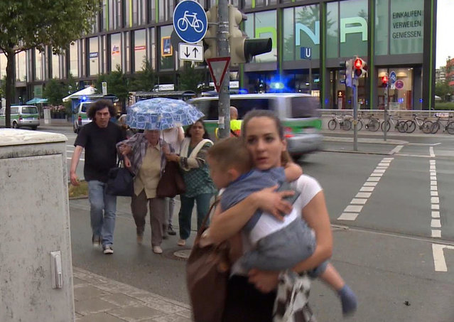 Members of the public run away from the Olympia Einkaufszentrum mall, after a shooting, in Munich, Germany, Friday, July 22, 2016. A manhunt was underway Friday for a shooter or shooters who opened fire at a shopping mall in Munich, killing and wounding several people, a Munich police spokeswoman said. The city transit system shut down and police asked people to avoid public places. (Photo by AP Photo)