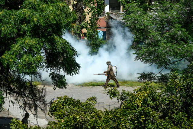 A worker sprays disinfectant in a residential area during a government-imposed nationwide lockdown as a preventive measure against the COVID-19 coronavirus, in Islamabad on April 10, 2020. (Photo by Aamir Qureshi/AFP Photo)
