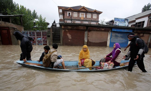 Residents leave a flooded neighborhood on a boat in Srinagar, India, Thursday, September 4, 2014. Authorities say heavy rains have triggered floods and landslides in the Indian portion of Kashmir, killing at least 14 people in the worst flooding in 22 years. (Photo by Mukhtar Khan/AP Photo)