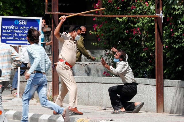 A police officer raises a baton at a man who, according to police, had broken the social distancing rule, outside a wine shop during an extended nationwide lockdown to slow the spread of the coronavirus disease (COVID-19), in New Delhi, India, May 4, 2020. (Photo by Adnan Abidi/Reuters)