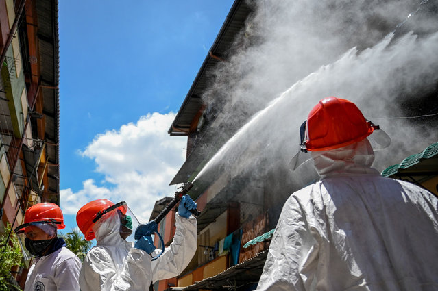 Municipal workers wearing protective gear spray disinfectant at an housing complex area during a government-imposed nationwide lockdown as a preventive measure against the COVID-19 coronavirus, in Colombo on April 17, 2020. (Photo by Lakruwan Wanniarachchi/AFP Photo)