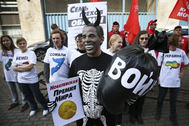 """A Russian Communist Party activist, wearing a mask depicting US President Barack Obama, holds a poster reading """"Nobel Peace Prize"""" in one hand and a bag reading """"War"""" in the other, takes part at a picket outside the UN mission in Moscow, Russia, Tuesday, September 9, 2014. The poster at the background reads: """"Seven Sins of Obama"""". Other participants wear tee shirts with writing in Cyrillic saying: Pakistan, Yemen, Somalia and Ukraine. (Photo by Pavel Golovkin/AP Photo)"""