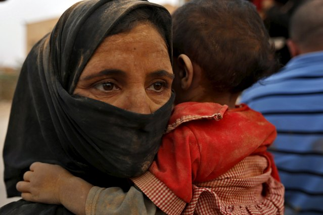 A Syrian refugee woman covered with dust carries her daughter after arriving at the Trabeel border, after she crossed into Jordanian territory with her family, near the northeastern Jordanian border with Syria, and Iraq, near the town of Ruwaished, east of Amman September 10, 2015. (Photo by Muhammad Hamed/Reuters)