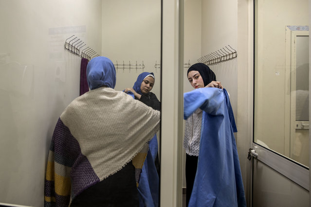 "Women who work at Egypt's agriculture and fruit exporting company, Gamco, get ready before work in the changing room at a factory, in the Mediterranean province of Alexandria, Egypt, Wednesday, April 15, 2020. Egypt has been listed as the world's largest exporter of orange, according to Aswaq financial company. ""Our exporting business to Europe is doing very well these days because people are in need of vitamin C and the demand is higher due to COVID-19"", says Gamco general manager Mohammed el-Sherif. (Photo by Nariman El-Mofty/AP Photo)"