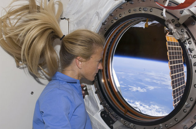 Astronaut Karen Nyberg looks through a window in the newly installed Kibo laboratory of the International Space Station on June 11, 2008. (Photo by Reuters/NASA)