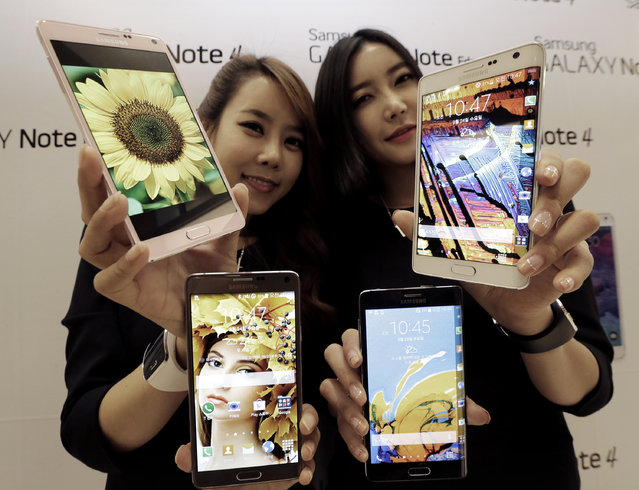 Models pose with Samsung Electronics Co.'s latest Galaxy Note 4 and Galaxy Note Edge smartphones during its unveiling in Seoul, South Korea, Wednesday, September 23, 2014. Samsung said Wednesday its latest Galaxy Note 4 smartphone will go on sale in China and South Korea later this week as its flagging mobile business tries to defend sales from Apple's new iPhones. (Photo by Ahn Young-joon/AP Photo)