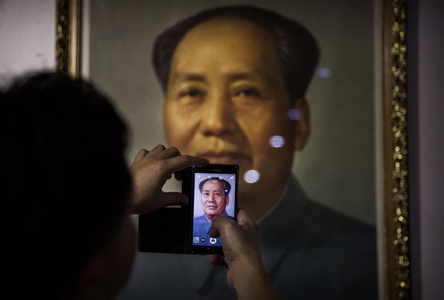 A Chinese collector takes a picture of a portrait of the late Mao Zedong at a sale and auction of memorabilia dedicated to him on September 19, 2014 in Beijing, China. Collectors from across China gathered for the event, which showcased valuable collectables of Mao, who 38 years after his death remains popular among many Chinese. (Photo by Kevin Frayer/Getty Images)