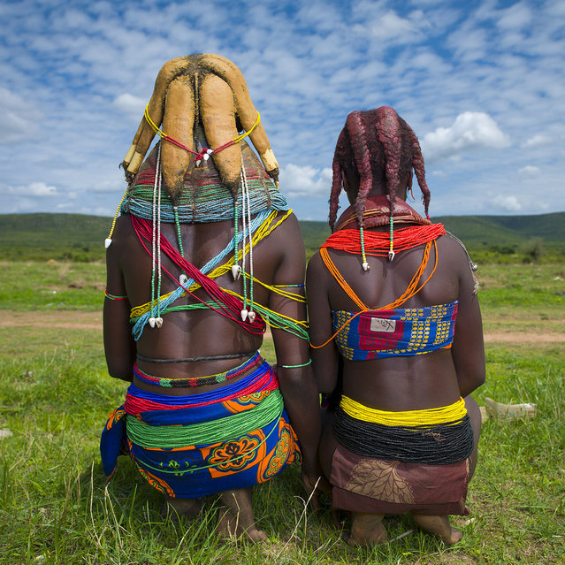 """Mwila tribe women backs – Angola. On the left, she is married , she wears the beads necklaces, and on the right, her sister is not yet married, as she wears the big red necklace"". (Eric Lafforgue)"
