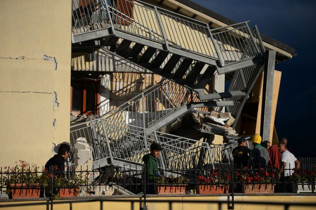 Residents look at a damaged home after a strong heartquake hit Amatrice on August 24, 2016. (Photo by Filippo Monteforte/AFP Photo)