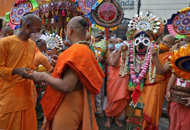 Hindu monks, wearing protective face masks, carry an idol of Hindu Lord Jagannath as part of a ritual after ISKCON (International Society of Krishna Consciousness) cancelled the annual Rath Yatra, or chariot procession, amidst the coronavirus disease (COVID-19) outbreak, in Kolkata, India, June 23, 2020. (Photo by Rupak De Chowdhuri/Reuters)
