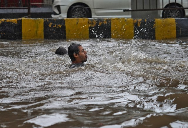 A man plays in a flooded road during heavy rains in Mumbai, India, July 4, 2020. (Photo by Hemanshi Kamani/Reuters)