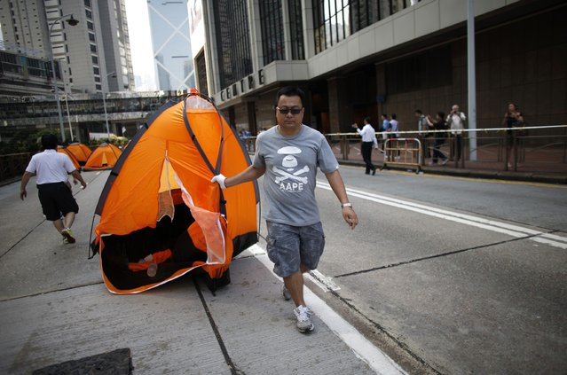 An Anti-Occupy Central protester drags away a tent at the main protest site in Admiralty in Hong Kong October 13, 2014. (Photo by Carlos Barria/Reuters)