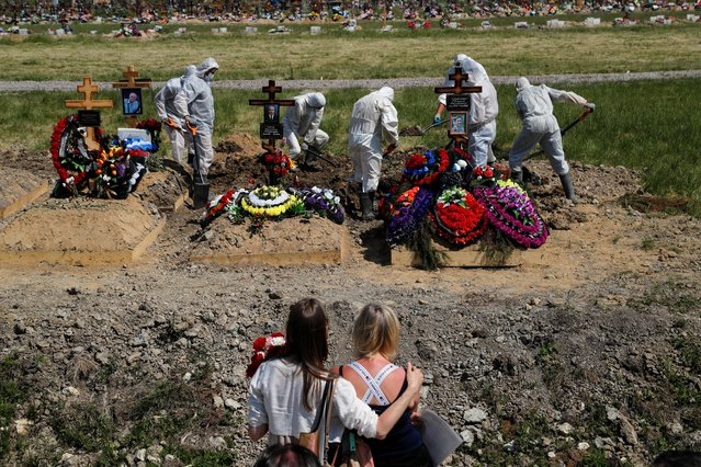 Mourners watch grave diggers burying a person, who presumably died of the coronavirus disease (COVID-19), in the special purpose section of a graveyard on the outskirts of Saint Petersburg, Russia on June 26, 2020. (Photo by Anton Vaganov/Reuters)