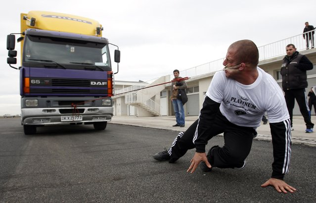 Lasha Pataraia pulls an eight-ton truck with his ear during a test event in Rustavi outside Tbilisi November 14, 2012. The 32-year-old sportsman will attempt to break a record registered by the Guinness Book of World Records by the end of the month, according to organisers. (Photo by David Mdzinarishvili/Reuters)