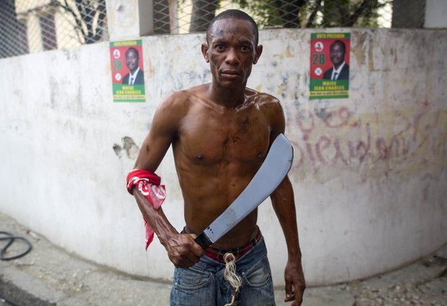 A supporter of Presidential candidate Moise Jean-Charles, from the Platform Pitit Dessalines party, holds a fake wooden machete as he readies to perform a dance during the opening of Jean-Charles' campaign in Arcahaie, Haiti, Sunday, August 28, 2016. Campaigning for Haiti's presidential redo election has gotten off to a very quiet start, with major candidates waiting for the weekend to hold their first events. Haiti's Provisional Electoral Council opened the 45-day campaign season Tuesday for 27 presidential candidates and various legislative hopefuls. (Photo by Dieu Nalio Chery/AP Photo)