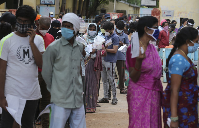 People wait in a queue to give their nasal swab samples to test for the coronavirus at Government Fever Hospital in Hyderabad, India, Wednesday, July 15, 2020. As India's coronavirus caseload approaches 1 million, lockdowns are being reimposed in parts of the country as governments try to shield the health system from being overwhelmed. (Photo by Mahesh Kumar A./AP Photo)
