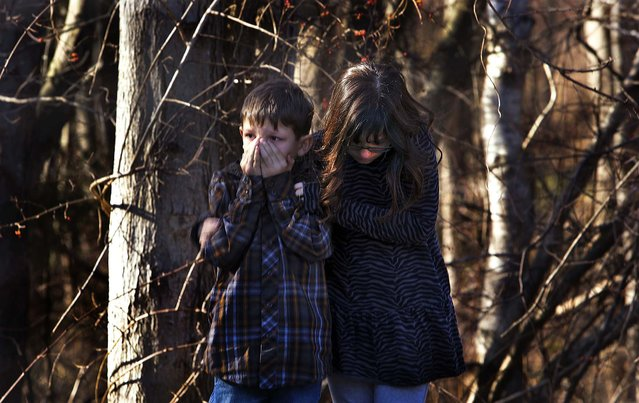Young children wait outside the school after the shooting. (Photo by Michelle McLoughlin/Reuters)