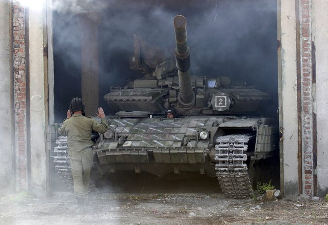 A member of the self-proclaimed Luhansk People's Republic (LNR) forces guides a tank to park after withdrawing it further from the frontline outside Luhansk, Ukraine, October 3, 2015. (Photo by Alexander Ermochenko/Reuters)