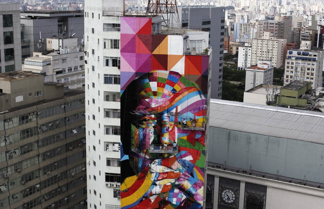 Brazilian graffiti artist Eduardo Kobra (C) puts the final touches to his piece of art in tribute to Brazilian architect Oscar Niemeyer, next to his assistants, at the financial center on Sao Paulo's Avenida Paulista January 22, 2013. Kobra created the 56-metre (61-yard) tall graffiti artwork as a tribute to Niemeyer, one of the 20th century's most influential modernist architects. Niemeyer died in December 2012, aged 104