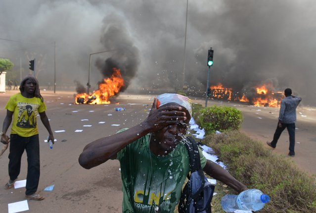 A protester rince his face outside the parliament in Ouagadougou on October 30, 2014 as cars and documents burn outside. Hundreds of angry demonstrators in Burkina Faso stormed parliament on October 30 before setting it on fire in protest at plans to change the constitution to allow President Blaise Compaore to extend his 27-year rule. (Photo by Issouf Sanogo/AFP Photo)