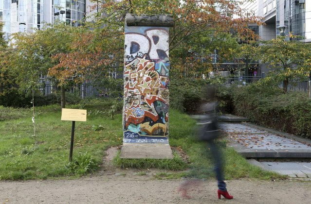 A woman walks past a piece of the Berlin Wall, which was from Potsdamer Platz, in a park outside the European Parliament in Brussels October 31, 2014. (Photo by Francois Lenoir/Reuters)