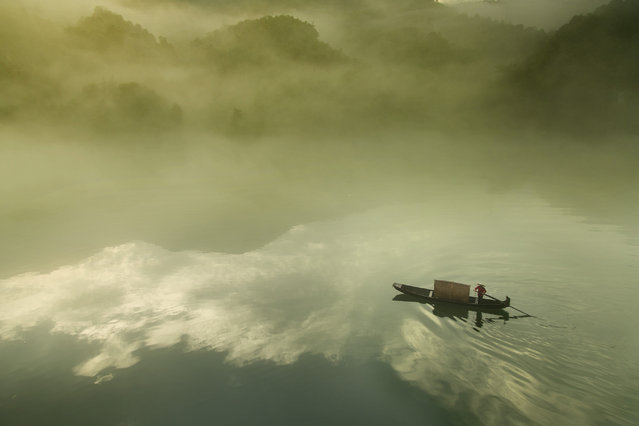 """""""The draw"""". The boat drawing in the morning fog. Photo location: Chenzhou, China. (Photo and caption by Lo Daniel/National Geographic Photo Contest)"""