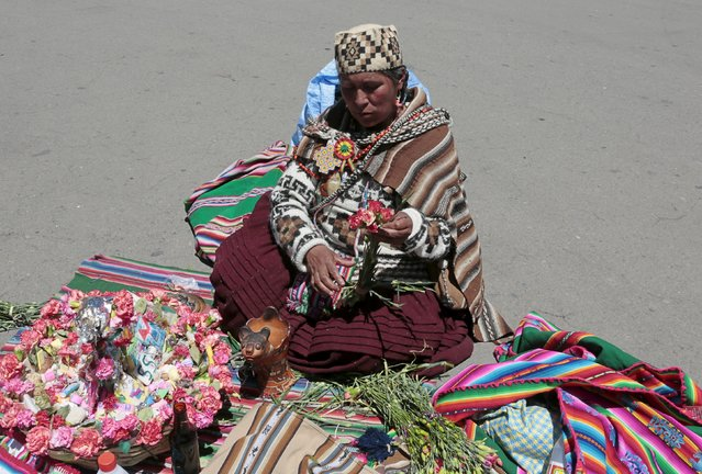 A witch doctor prepares an offering for the inauguration of the World People's Conference on Climate Change and the Defense of Life, prior to the World Climate Change Conference, in Tiquipaya, Bolivia, October 10, 2015. (Photo by David Mercado/Reuters)