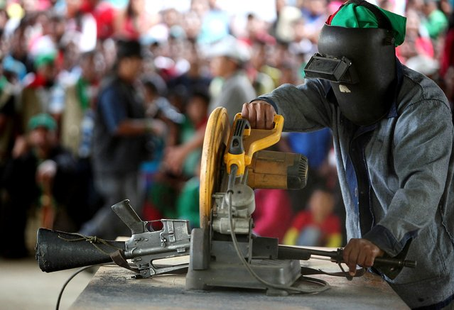 A gun belonging to FARC rebels, who are accused of murder, is destroyed as they are presented to the media in Toribio, Cauca November 9, 2014. Leftist FARC guerrillas killed two members of an indigenous community in southwestern Colombia on Wednesday apparently for removing a billboard commemorating the death of their former leader Alfonso Cano in the region three years ago, police said. (Photo by Reuters/Stringer)