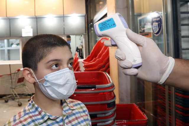 A worker checks a boy's body temperature at the entrance to a shopping center in Baghdad, Iraq, August 13, 2020. The Iraqi Health Ministry on Thursday recorded 3,841 new COVID-19 cases, the highest daily increase since the outbreak of the disease, as the health officials warned of a higher number of infections in the coming days. (Photo by Khalil Dawood/Xinhua via Getty Images)