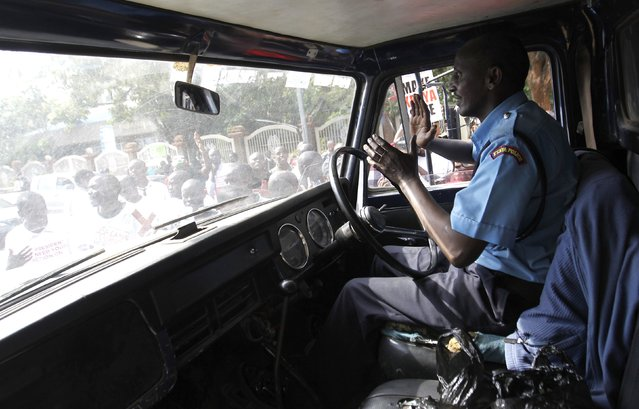 A police driver negotiates with protesters blocking traffic during the #OccupyHarambeeAve demonstration in Kenya's capital Nairobi November 25, 2014. (Photo by Thomas Mukoya/Reuters)