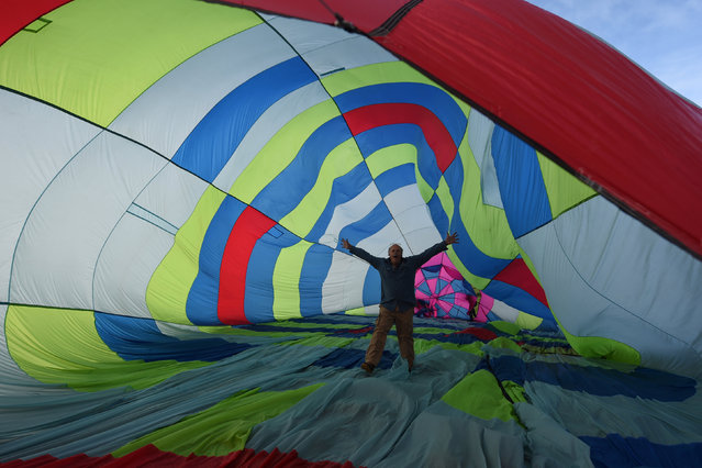 A man walks through the inside of a balloon during the Irish hot air ballooning championships in Galway, Ireland September 26, 2016. (Photo by Clodagh Kilcoyne/Reuters)