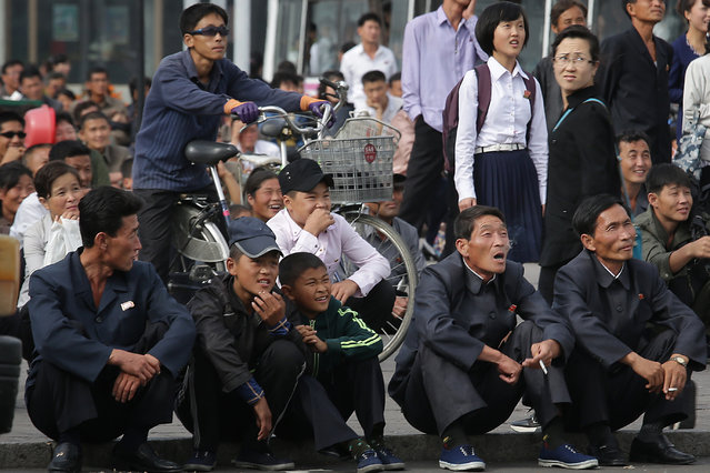 North Koreans react, some smiling as they watch a movie shown on a giant screen in a public square near the Pyongyang train station on Wednesday, September 28, 2016, in Pyongyang, North Korea. (Photo by Wong Maye-E/AP Photo)