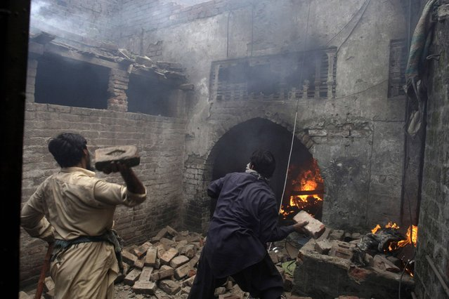 Pakistani men, part of an angry mob, throw bricks at a Christian house after setting it on fire, in Lahore, Pakistan, Saturday, March 9, 2013. A mob of hundreds of people in the eastern Pakistani city of Lahore attacked a Christian neighborhood Saturday and set fire to homes after hearing accusations that a Christian man had committed blasphemy against Islam's prophet, said a police officer. (Photo by K.M. Chaudary/AP Photo)