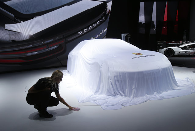A worker adjusts the sheet around a car at the Porsche stand during the Paris Motor Show in Paris, France on Thursday, September 29, 2016. (Photo by Michel Euler/AP Photo)