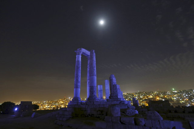 The moon is seen over the Roman pillars of the Temple of Hercules as it is lit up in blue to mark the 70th anniversary of the United Nations at the Citadel in Amman, Jordan, October 24, 2015. (Photo by Muhammad Hamed/Reuters)