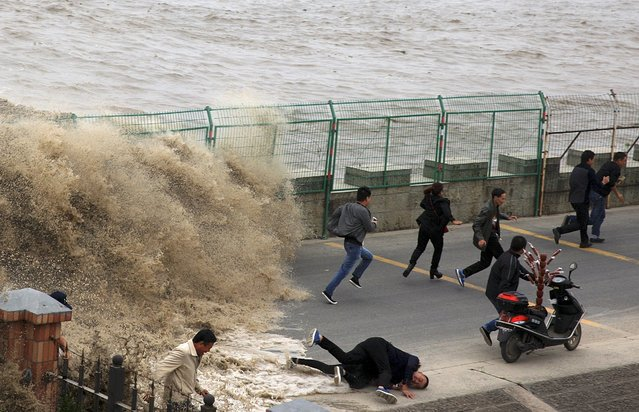 A visitor falls down as they run away from a wave caused by a tidal bore which surged past a barrier on the banks of Qiantang River, in Hangzhou, Zhejiang province, China, October 28, 2015. (Photo by Reuters/China Daily)