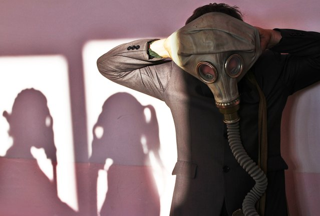 A Belarus senior school pupil wears a gas mask during a fire safety drill at a school in the village of Krevo, some 100 kilometers northwest from Minsk, on December 2, 2014. (Photo by Sergei Gapon/AFP Photo)
