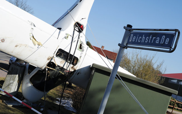 A sports airplane stands on its nose after an emergency landing next to a power box and a streetlamp in Haselau, northern Germany, on April 2,  2013. The 52-year-old somehow escaped with minor injuries after smashing into land just feet from a row of houses in Haselau on Tuesday. His 23-year-old daughter, who was a passenger, also survived the terrifying incident relatively unscathed. Die Welt newspaper reports the aircraft suffered technical problems during the flight, forcing the pilot to perform an emergency landing. The plane came to a stop against a lamppost after being guided to the ground. Strong winds then blew the plane onto its nose, after the pair had left the wreckage. (Photo by Angelika Warmuth/AFP Photo)