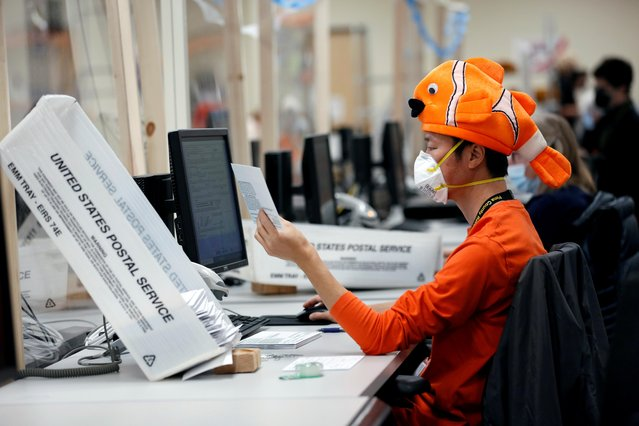 An employee wears a halloween costume while processing early voting and absentee ballots ahead of the upcoming presidential election in Tucson, Arizona, October 31, 2020. (Photo by Cheney Orr/Reuters)