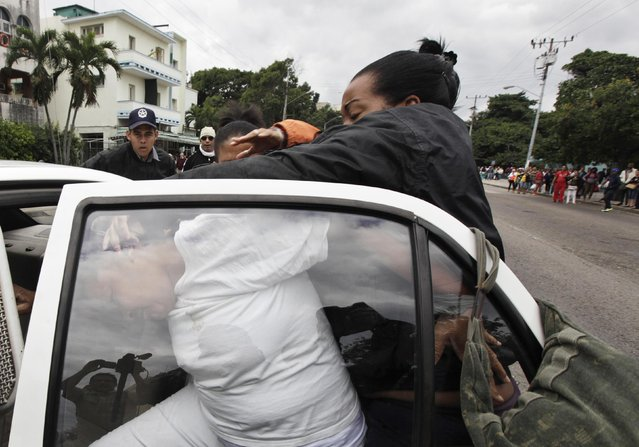 Cuban security personnel detain a supporter of the Ladies in White group during a protest on International Human Rights Day, in Havana December 10, 2014. (Photo by Enrique De La Osa/Reuters)